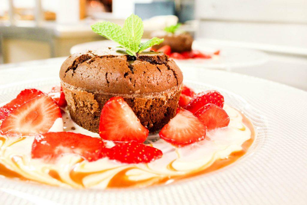 Schokoladentörtchen mit frischen Erdbeeren auf Saucenmalerei